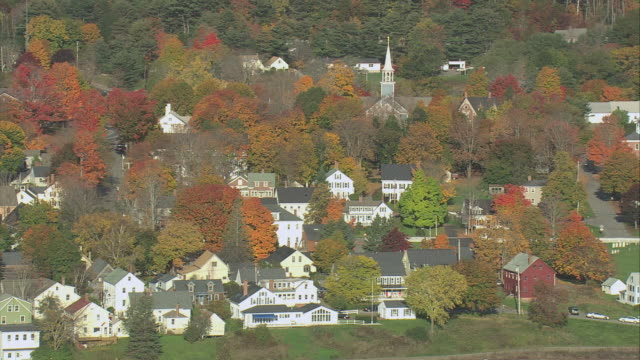 AERIAL Small town nestled among fall colored trees at the end of a long low highway bridge over the Sheepscot River / Wiscasset, Maine, United States