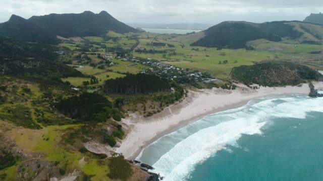 small town next to ocean beach, whangarei heads, new zealand. - baia delle isole nuova zelanda video stock e b–roll