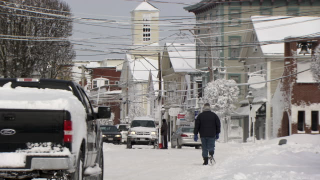 Small town street scene with cars and pedestrians after a snowstorm