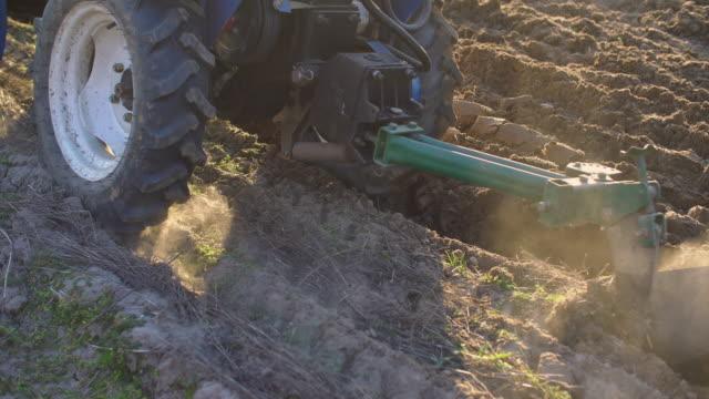vídeos y material grabado en eventos de stock de un pequeño tractor está arar la tierra - arar