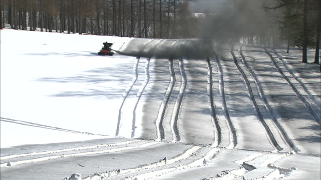 Small tractor spraying cloud of snow melting material over golf course, Hokkaido