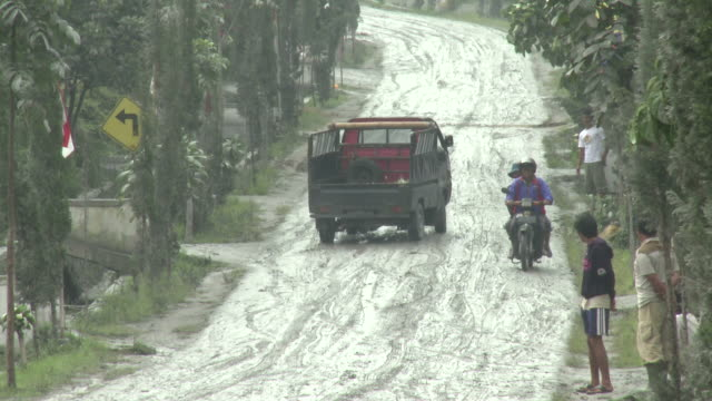small truck struggles up hill coated in volcanic ash mud, helper, after merapi volcano eruption; indonesia. 7 november 2010 / audio - schlamm stock-videos und b-roll-filmmaterial