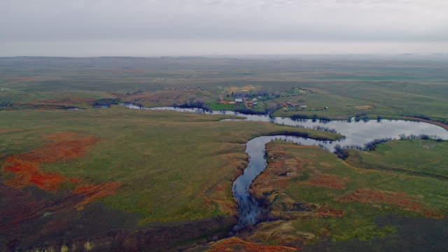 small village at the shore of a lake near jordan, montana, in early spring in the morning. overcast weather with a soft light. aerial drove video with the wide-orbit, panoramic camera motion. - grass area stock videos & royalty-free footage