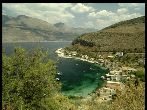 Small village at waters edge mountains in background trees in foreground Peloponnese Greece