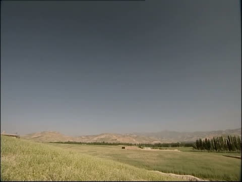 stockvideo's en b-roll-footage met a small village lies in a wide grassy valley in the afghanistan desert. - afghanistan