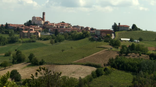 small village with a church surrounded by vineyards in summer on a hot and sunny day - piemonte video stock e b–roll