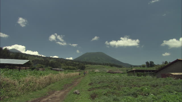 WS Small village with sheds and barns in mountain landscape, conical volcano in background / Volcanoes National Park, North Province, Rwanda