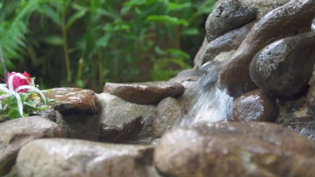 a small waterfall at a hotel resort. - klein stock-videos und b-roll-filmmaterial