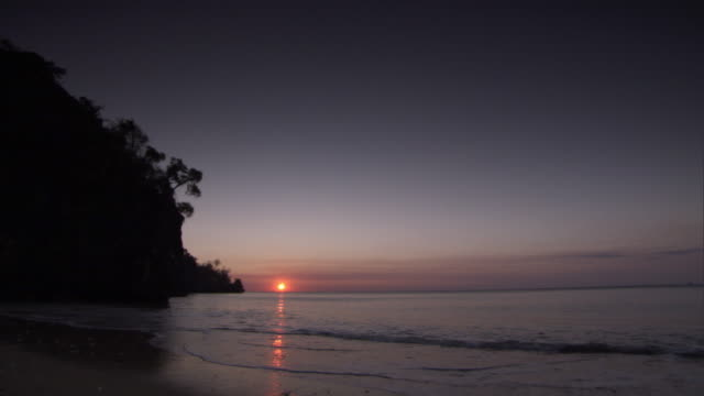 Small waves break onto beach at sunset, Madagascar