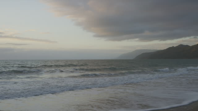 small waves wash up on beach as sun sets over ocean - small stock videos and b-roll footage