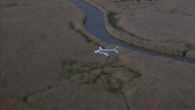 A small, white plane flies low over lakes and rivers on the African plains in this aerial, tracking shot.