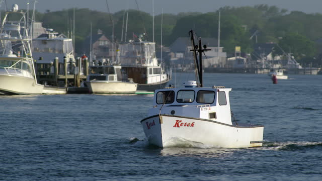 Small white shell-fishing or lobster boat leaving quaint New England fishing village