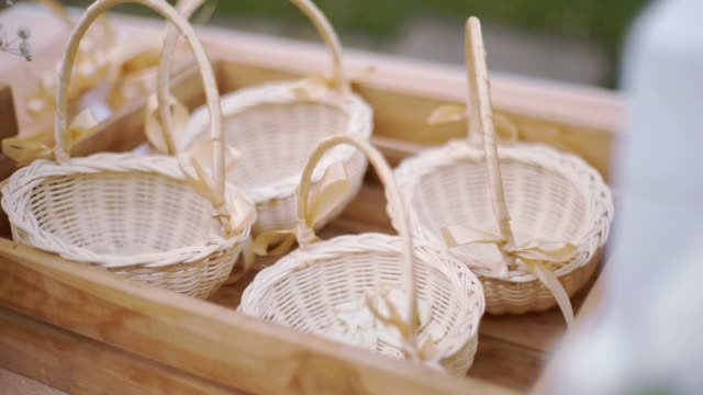 small wicker baskets with ribbons in a wooden tray at outdoor party. - wicker stock videos & royalty-free footage