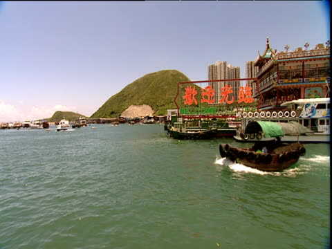 small wooden boat with canopy passes hill and buildings in background hong kong - non western script stock videos & royalty-free footage