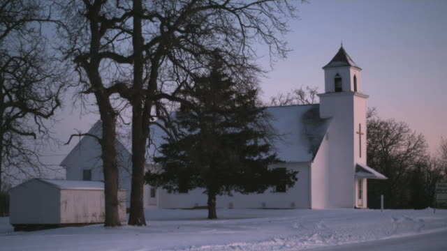 WS Small wooden church in snow-covered rural landscape, Iowa, USA