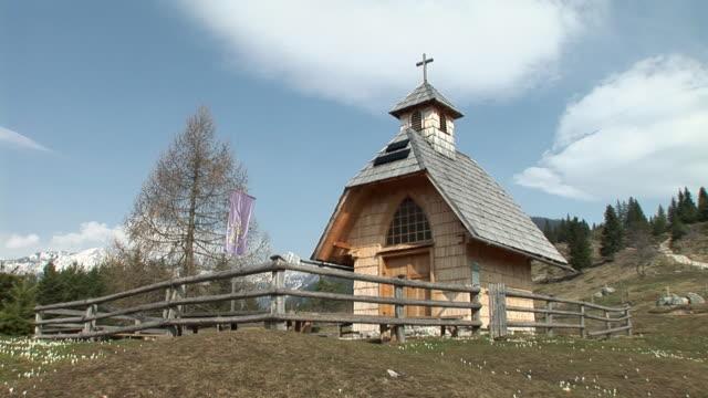 vídeos de stock e filmes b-roll de ws, la, small wooden church on meadow, uskovnica, bohinj, slovenia - vedação