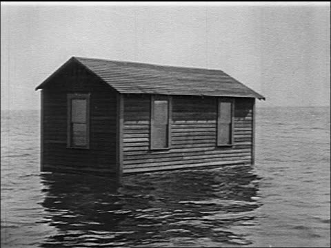 b/w 1916 small wooden house floating on ocean - orizzonte sull'acqua video stock e b–roll