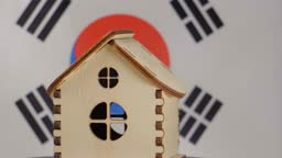 Small wooden house, Republic of Korea flag on background. Real estate concept, soft focus