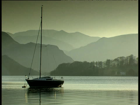 small yacht anchored on lake with grey mountains in background - anchored stock videos & royalty-free footage