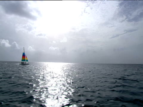 small yacht with rainbow sails across water sun shining through clouds and reflecting on the sea tobago - menschlicher arm stock-videos und b-roll-filmmaterial