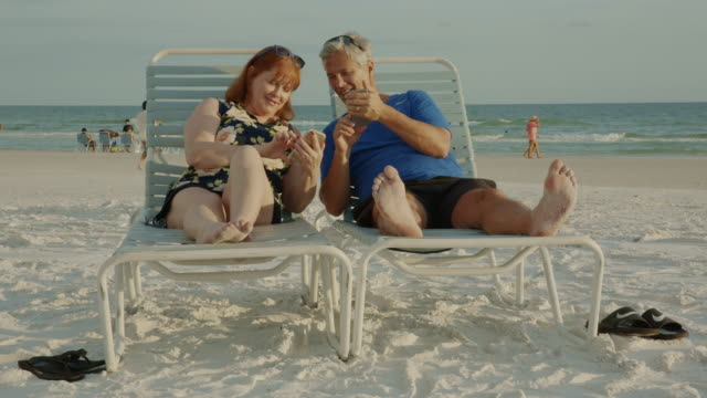 smarphone senior couple social media florida beach - chair stock videos & royalty-free footage