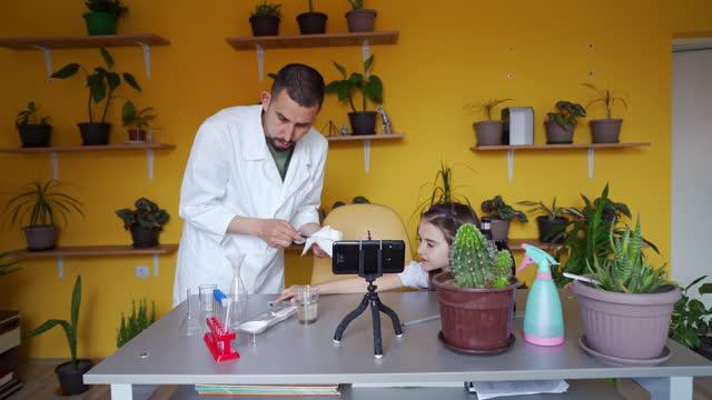 intelligente und neugierige mädchen, hilft ihrem onkel, einen pädagogischen inhalt für seinen wissenschaftskanal in seinem haus improvisiert labor aufzeichnen - content stock-videos und b-roll-filmmaterial