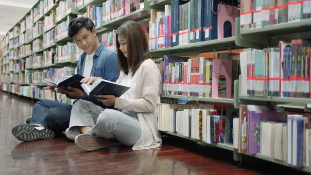smart asian mann und frau universität student lesen buch zwischen bücherregalen in campus-bibliothek mit kopierraum. - literatur stock-videos und b-roll-filmmaterial