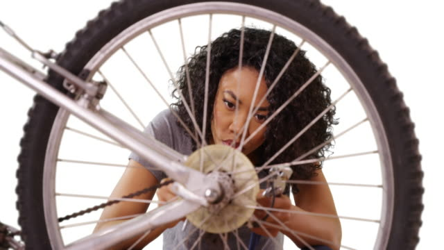 smart black female expertly repairing bike on white background - wrench stock videos & royalty-free footage