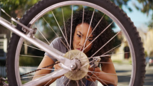 smart black female fixing bicycle wheel in suburban neighborhood - wrench stock videos & royalty-free footage