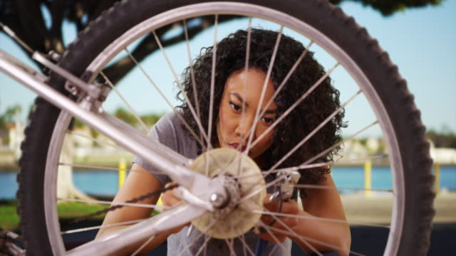 smart black female repairing bicycle wheel in outdoor setting - wrench stock videos & royalty-free footage