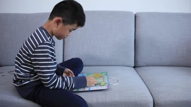 vidéos et rushes de garçon intelligent jouant la carte faite de pièces de puzzle - curiosité