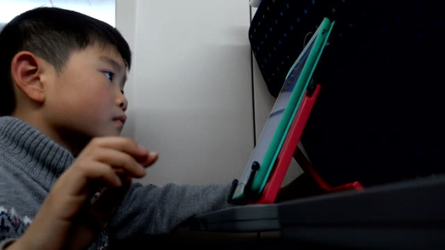 smart boy mit digitalem tablet im hochgeschwindigkeitszug - bahnreisender stock-videos und b-roll-filmmaterial