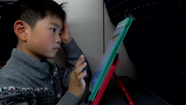 vidéos et rushes de garçon intelligent utilisant la tablette numérique dans le train à grande vitesse - passager
