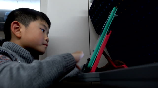 高速列車でデジタルタブレットを使用してスマート少年 - 高速列車点の映像素材/bロール