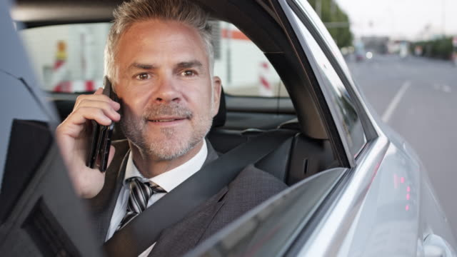 smart business man in full suit gets chauffeured through the city on business trip and using smart phone - geld verdienen stock-videos und b-roll-filmmaterial