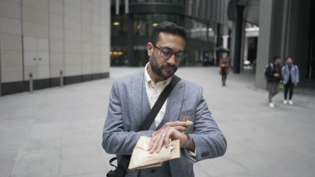 vidéos et rushes de a smart business man on the go. walking and eating at the same time. - sandwich