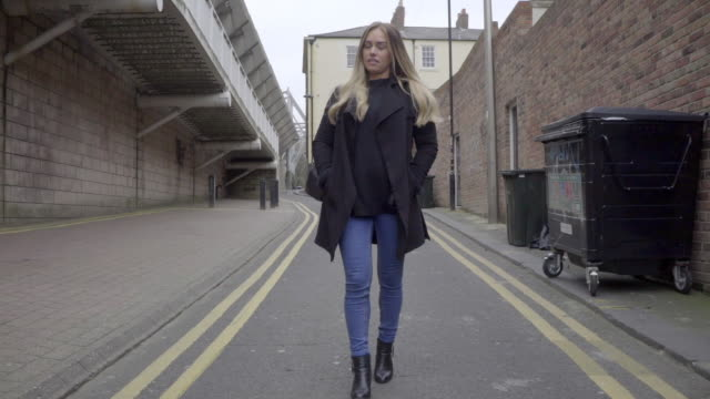 smart casual attractive blonde woman walks alone in alley - trousers stock videos & royalty-free footage