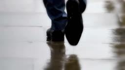 Smart city shoes, businessmen walking in rain. Feet only, rear view.