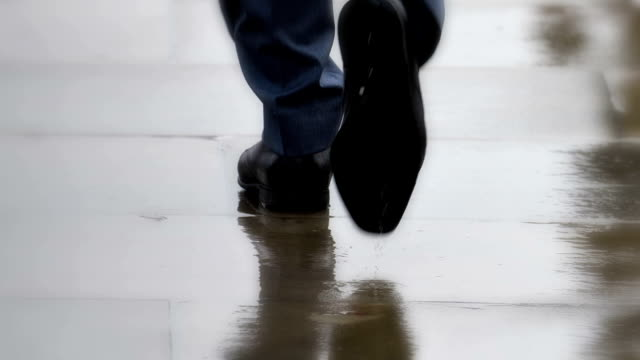 vídeos de stock e filmes b-roll de smart city shoes, businessmen walking in rain. feet only, rear view. - passos