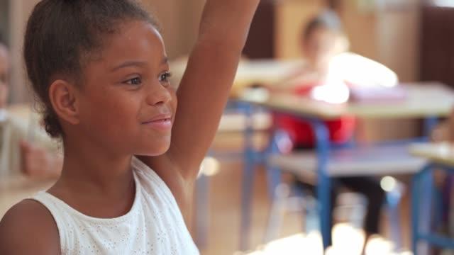 vídeos y material grabado en eventos de stock de inteligente diversa colegiala levantando la mano para que pueda dar la respuesta a la pregunta del maestro - alzar la mano