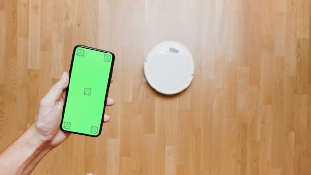 a smart phone controlling an intelligent robotic vacuum cleaner at home - vacuum cleaner stock videos & royalty-free footage