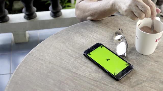 4k: smarta telefonen på bordet i morgon. - människofinger bildbanksvideor och videomaterial från bakom kulisserna
