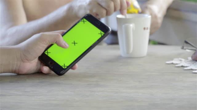 vidéos et rushes de 4k: téléphone intelligent sur la table dans la matinée. - portability