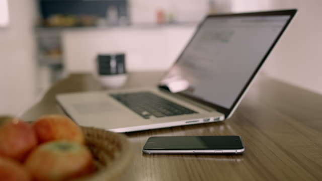 cu smart phone on table next to laptop - still life stock videos & royalty-free footage