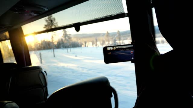 vídeos de stock, filmes e b-roll de telefone inteligente tiro vídeo de execução em uma neve estrada coberta com pneu faixas em direção uma árvore durante o inverno em arjeplog, suécia - smart