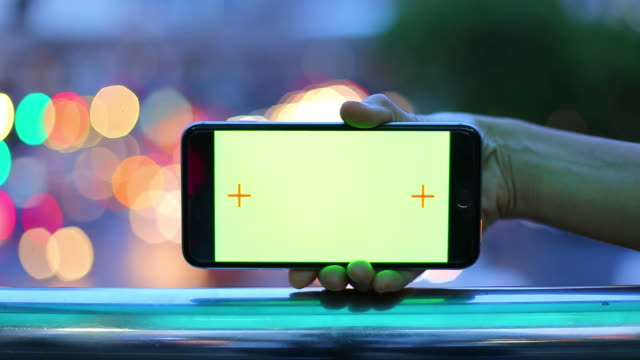 smart phone with green screen and bokeh light from traffic