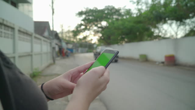 Smart phone with green screen on dusk street