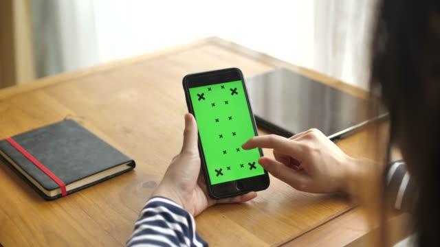 vídeos de stock, filmes e b-roll de telefone inteligente com tela verde - rolando