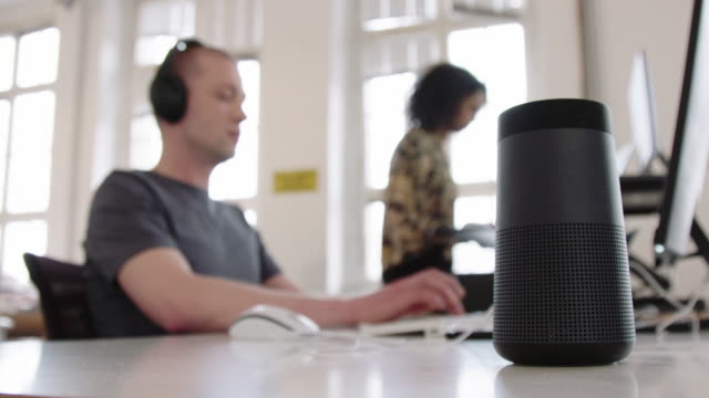 smart speaker device on desk with people working in office - bluetooth stock videos & royalty-free footage