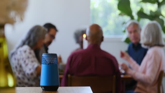 smart-lautsprecher auf dem tisch mit freunden im hintergrund - tischflächen aufnahme stock-videos und b-roll-filmmaterial